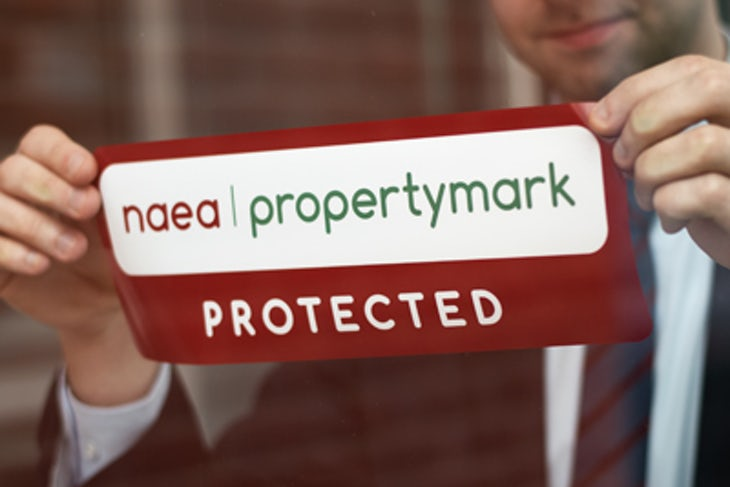 man sticking a NAEA Propertymark sticker on a window