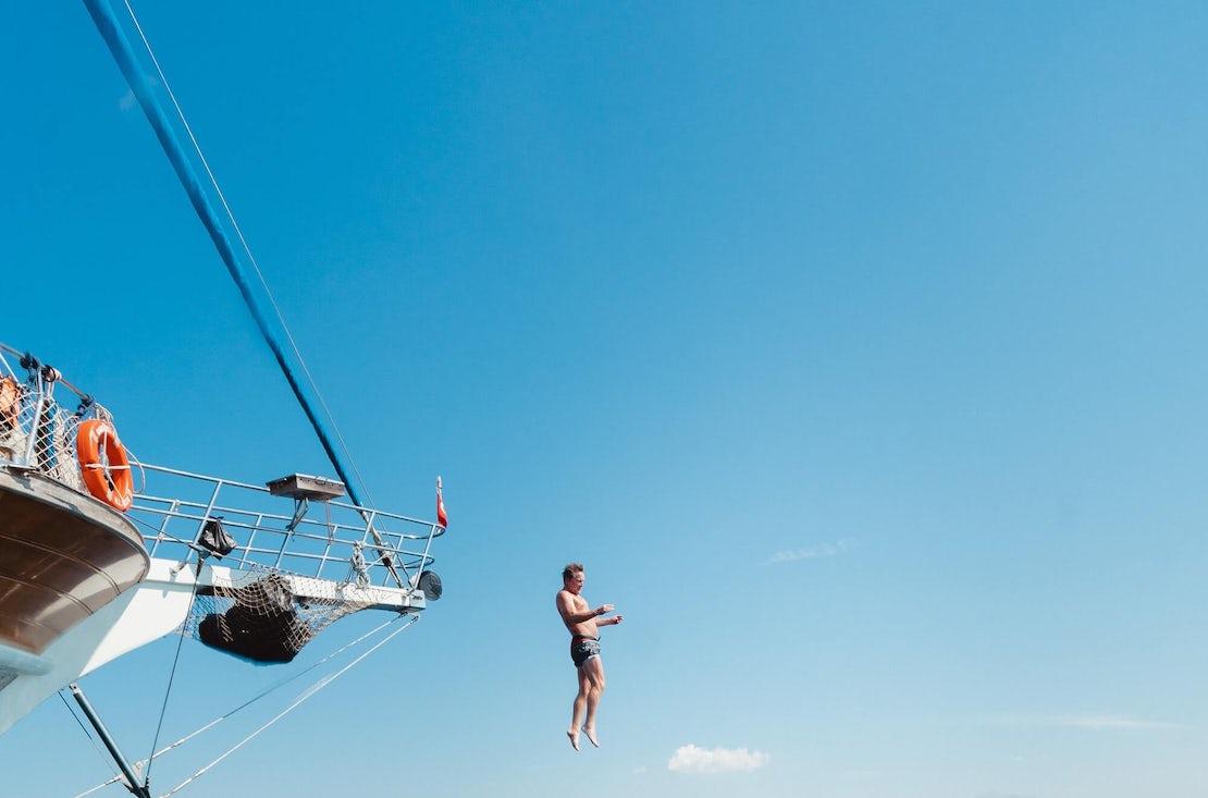man jumping into an ocean