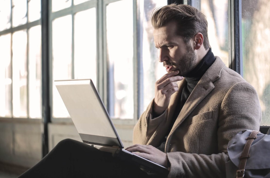 man in coat sitting looking at a laptop