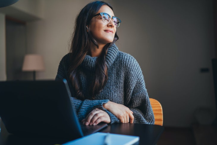 Happy attractive young woman working in modern office using laptop, businesswoman in casual wear working from home office on new product development strategy
